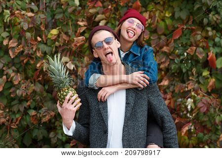 Happy young couple posing on the camera on the nature background. Pretty girl in a red cap standing near the boy and boy holds pineapple. Close-up of couple.