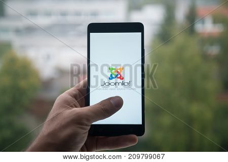London, United Kingdom, october 3, 2017: Man holding smartphone with Joomla logo with the finger on the screen
