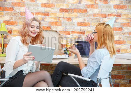 Beautiful girl eating pizza in the office in front of a laptop with a drink in her hand