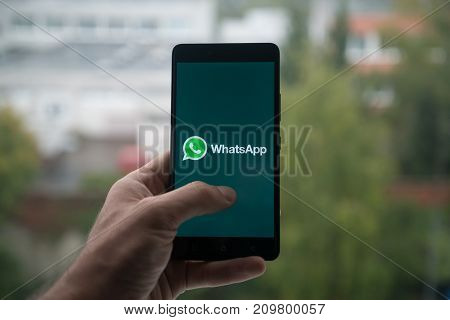 London, United Kingdom, october 3, 2017: Man holding smartphone with Whatsapp logo with the finger on the screen