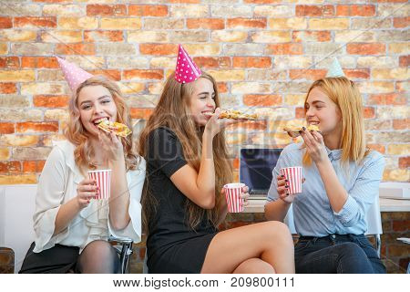 A company of three girls eat pizza at the office of a holiday which is a holiday