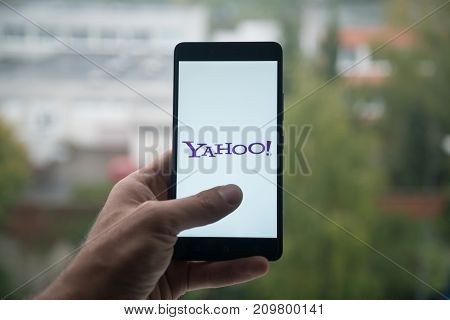 London, United Kingdom, october 3, 2017: Yahoo Man holding smartphone with  logo with the finger on the screen