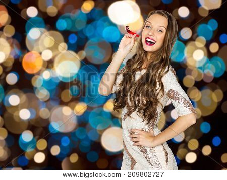 holidays, celebration and people concept - happy young woman or teen girl in fancy dress with sequins and party blower over festive lights background