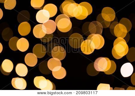 holidays and luxury concept - blurred golden lights over dark background