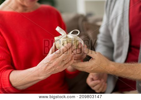 christmas, holidays and people concept - close up of senior couple with gift box at home
