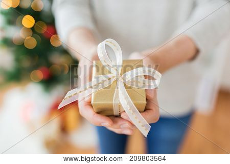 christmas, holidays and people concept - close up of male hands with gift box