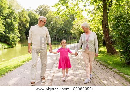 family, generation and people concept - happy smiling grandmother, grandfather and little granddaughter walking at park