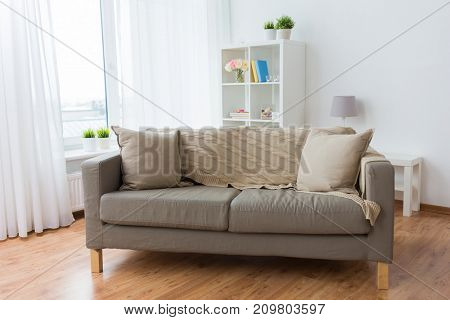 comfort, furniture and interior concept - sofa with cushions at cozy home living room