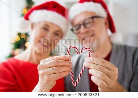 christmas, holidays and people concept - close up of happy smiling senior couple in santa hats with heart of candy canes at home