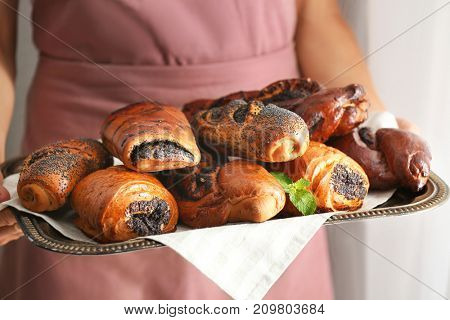 Woman holding tray of tasty pastries with poppy seeds, close up