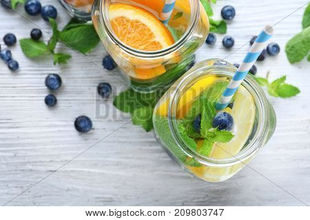 Mason jars of infused water with fruits on wooden table