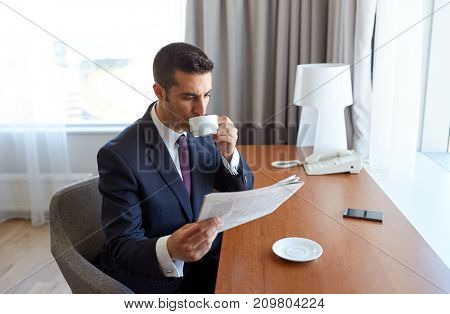 business trip, people and mass media concept - businessman reading newspaper and drinking coffee at hotel room