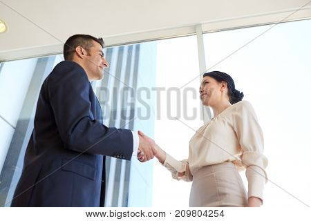 business, partnership and people concept - smiling man and woman shaking hands at office