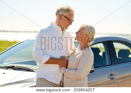 road trip, travel and old people concept - happy senior couple at car in summer