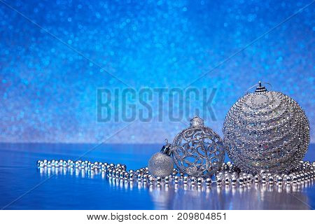 Christmas decoration with silver balls, gift box and garlands lying on a blue background. New year and Christmas background with copy space for text. Greeting card.
