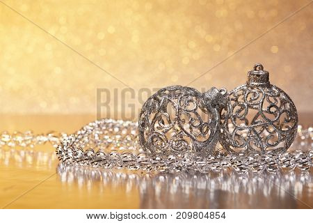 Christmas decoration with silver balls and garlands lying on a golden background. New year and Christmas background with copy space for text. Greeting card.