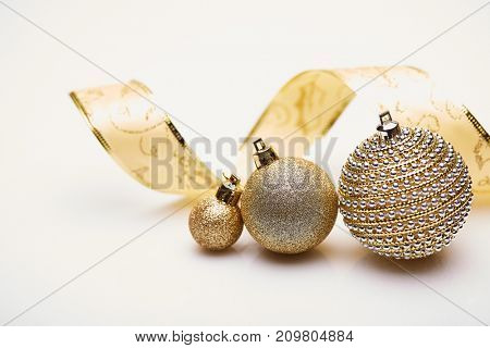 Christmas ornament with golden balls and decorative tape on a white background. New year and Christmas background with copy space for text. Greeting card.