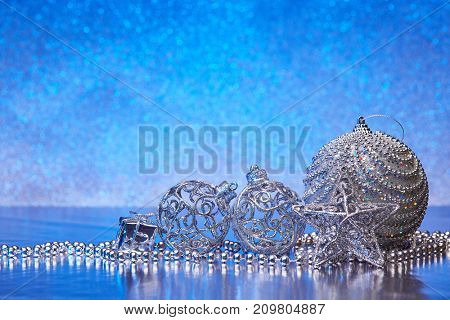 Christmas decoration with silver balls, star, gift box and garlands lying on a blue background. New year and Christmas background with copy space for text. Greeting card.