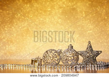 Christmas decoration with silver balls, star, gift box and garlands lying on a golden background. New year and Christmas background with copy space for text. Greeting card.