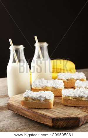 Wooden board with pieces of tasty banana cake and two bottles of milk on table