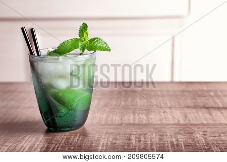 Glass of cocktail with lime and mint on wooden table