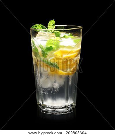 Glass of cocktail with mint and lemon on black background