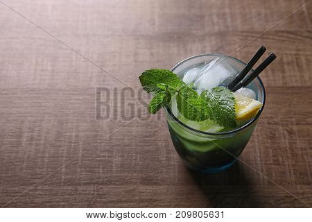 Glass of cocktail with lemon and mint on wooden background