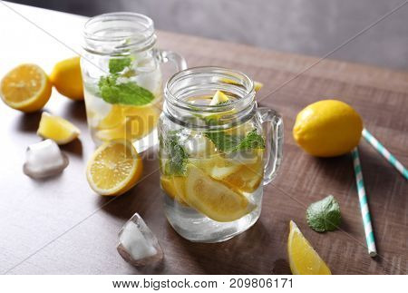 Mason jars with mojito cocktail on wooden table
