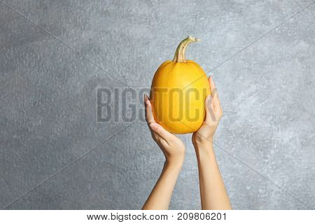 Woman holding ripe spaghetti squash on light background