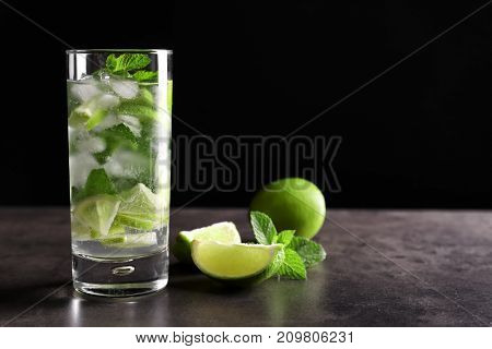 Glass of cocktail with lime and mint on table