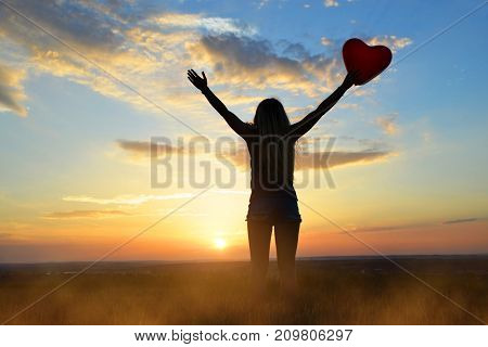 Silhouette of women holding balloon in heart shape in hand at sunset.