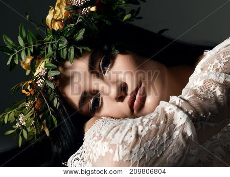 Beautiful portrait of young woman with wreath of flowers lying on a floor on dark background