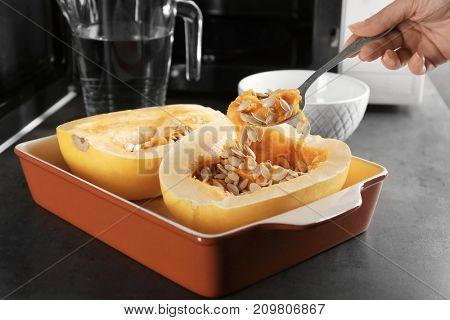 Woman preparing spaghetti squash on table