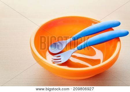Bright baby tableware on wooden table