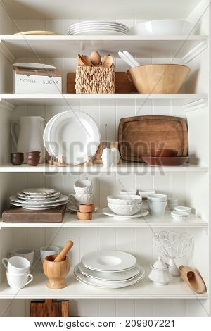 Storage stand with tableware and kitchen utensils indoors