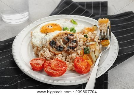 Plate with oatmeal, fried egg, mushrooms and vegetables on table