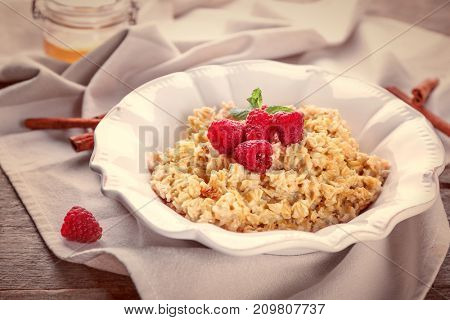 Plate with oatmeal and raspberries on table