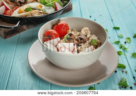 Bowl with oatmeal, mushrooms and vegetables on table