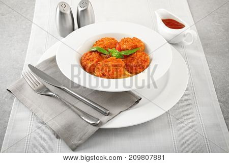 Plate with tasty sausage balls and pasta on table
