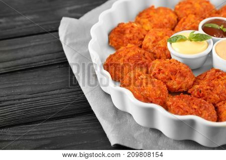 Baking dish with tasty sausage balls and sauces on table