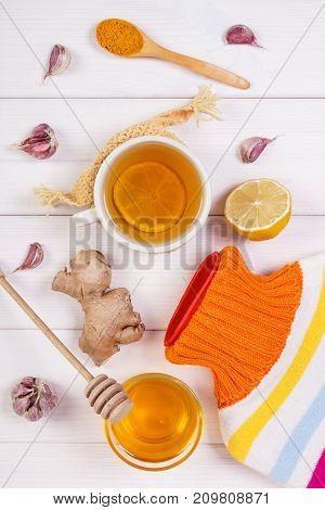 Hot Water Bottle, Cup Of Hot Tea And Ingredients For Preparation Warming Beverage