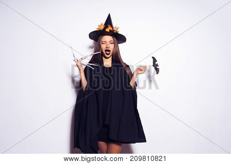 girl in witch costume winks against white background