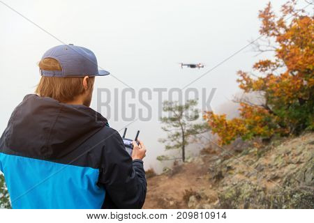 Young man handling drone, using remote control. New technology and trends in photo and video recording.