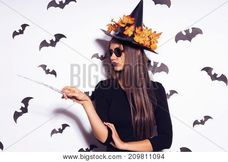 girl in a witch costume with glasses surrounded by bats