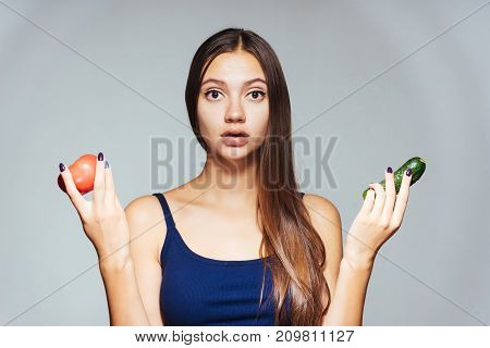 surprised girl holding a cucumber with a tomato