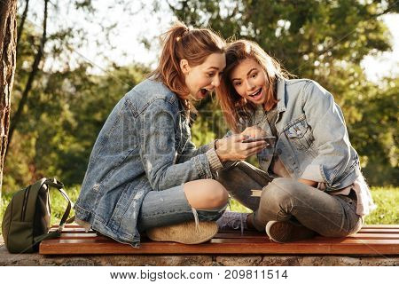 Two amazed female friends sitting on wooden bench with crossed legs, looking at smartphone in park