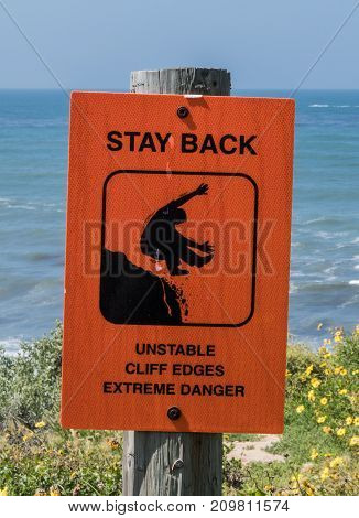Unstable Cliffs Warning Sign on wooden post over cliff near ocean side