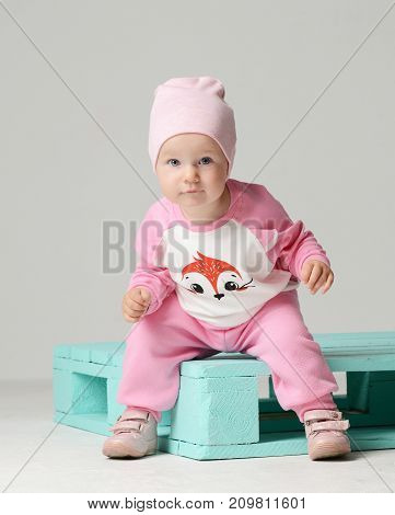 Infant child baby kid girl toddler sitting in pink hat and looking at the camera happy  smiling on gray background
