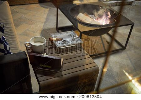 Small wooden cigar table with humidor, ashtray with burning cigar, cup of coffee near sofa and portable fireplace with firewoods.