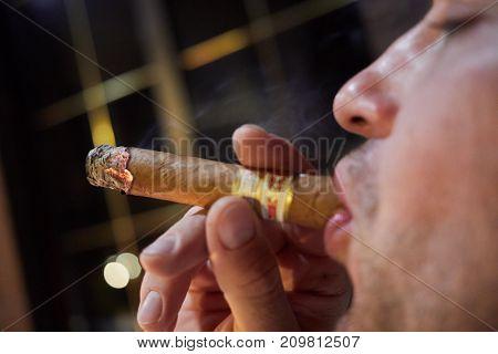 Closeup face in profile of man smoking cigar.